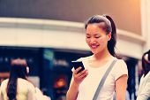 beautiful young asian woman using smart phone on shopping street