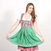 Woman posing in dirndl dress against a white wall