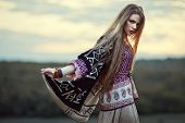 stock photo of hippy  - Beautiful hippie girl outdoors at sunset. Boho fashion style