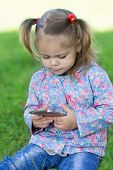 Little girl sitting on grass and using a smartphone. Two years.