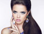 stock photo of long nails  - Beautiful Brunette young woman with fashion earring - JPG