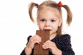Charming little girl eating chocolate. Two years.