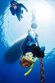 stock photo of descending  - Lady free diver descending along the metal chain using his hands  - JPG