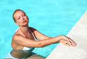 Young Female Enjoying Sun In Swimming Pool