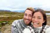 Iceland couple selfie wearing Icelandic sweaters in beautiful nature landscape on Iceland. Woman and man model in typical Icelandic sweater. Multiracial couple, Asian woman, Caucasian man.