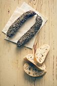 dried sausage with peppercorn and ciabatta on old table