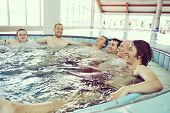 Group of friends in a swimming pool enjoying their holidays