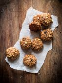 pic of baked raisin cookies  - Homemade oatmeal cookies with raisins and peanuts on a rustic wooden table - JPG