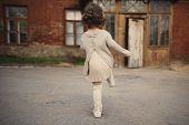 foto of girl walking away  - cute little girl walking away street photo - JPG