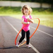 little girl learns to spin the Hoop