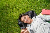 Portrait of Asian student lying on the green grass, doing use mobile phone