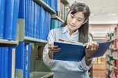 Asian Student Reading Book In Library At University
