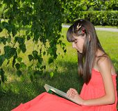 Girl in a red dress is reading a book