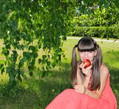 Girl in red dress eating an apple