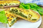 Pie with spinach and cheese in plate on board
