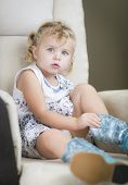 stock photo of baby cowboy  - Adorable Blonde Haired Blue Eyed Little Girl Putting on Cowboy Boots - JPG