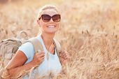 Portrait of cheerful smiling woman sitting in beautiful golden wheat field, travel with backpack alo