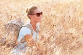 Happy cheerful woman sitting in beautiful golden wheat field, travel with backpack along Europe, act
