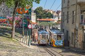 LISBON, PORTUGAL - September 29, 2014: Very touristic place in downtown Lisbon, Gloria Funicular (National Monument) with a traditional tram passing by in the city of Lisbon, Portugal.