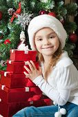 Smiling Little Girl In Santa Hat With Gifts