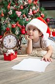 Dreaming Little Girl In Santa Hat Writes Letter To Santa Claus