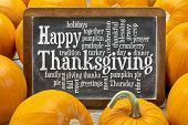 foto of thanksgiving  - Happy Thanksgiving word cloud on a  vintage slate blackboard surrounded by pumpkins - JPG