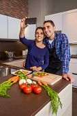 Couple in kitchen cooking and taking selfie with smartphone