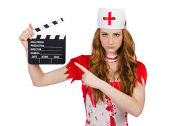 pic of witch-doctor  - Woman doctor in bloody uniform with movie clapperboard - JPG