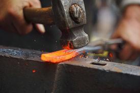 stock photo of anvil  - Detail shot of hammer forging hot iron at anvil - JPG