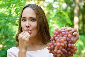 picture of slender  - Beautiful slender girl eating healthy fruit - JPG
