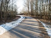 stock photo of icy road  - icy winter road with sun rays and trees - JPG