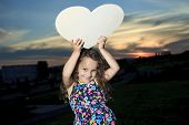 A little girl holding a heart on the sunset