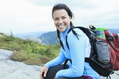 Female hiker with backpack walking and smiling on a country trai