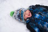 Cheerful Boy Playing In Snow Angel