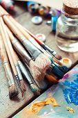 Vintage Stylized Photo Of Paintbrushes Closeup, Artist Palette And Multicolor Paint Tubes.