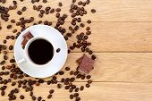 Cup Of Black Coffee, Chocolate And Coffee Beans On A Wooden Background