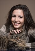 stock photo of cuddle  - Beautiful woman cuddling a cat and smiling at camera - JPG