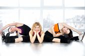 Team Of Three Females Posing, Sitting In Splits In Fitness Class