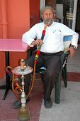 The older man smokes a hookah