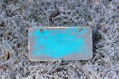 Blank wooden sign with ice covered grass background