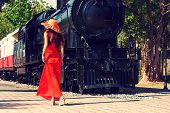 Young woman in red dress waiting train on the platform of railway station. Retro style