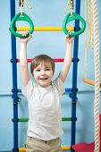 child hanging on gymnastic rings