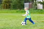 stock photo of cute kids  - Active cute little kid boy playing soccer and football and having fun outdoors on field. Active leisure with children on warm sunny summer day. ** Note: Soft Focus at 100%, best at smaller sizes - JPG