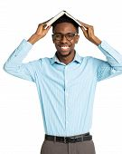 Happy African American College Student With Book On His Head Standing On White