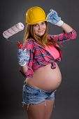 Young Beautiful Pregnant Woman In Builder's Helmet With  Paint Brush Over Grey