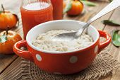picture of porridge  - Porridge in an orange bowl juice and mandarins on the table