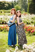 Two beautiful happy pregnant women friends. outdoor. against the background of flowers