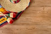 pic of mexican fiesta  - Mexican background with sombrero straw hat maracas and traditional serape blanket or rug on a wood floor - JPG