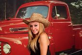 Country girl in front of an old pickup truck