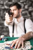 stock photo of guns  - View of a gangster man is playing poker and holding a gun. Focus on a gun.
